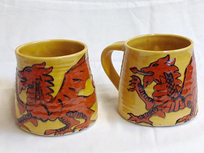 two yellow mugs with dragon design